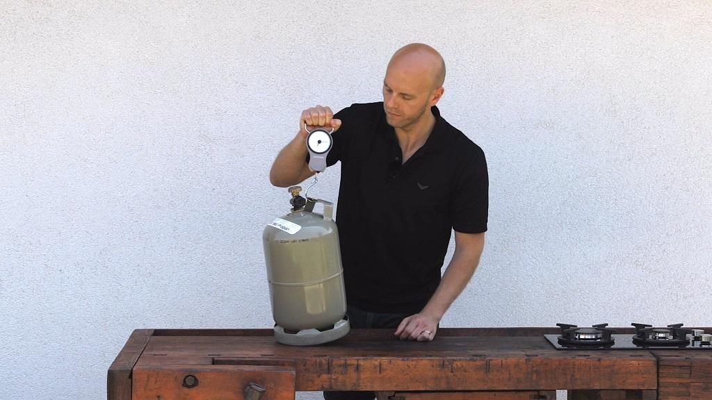 Mit einer Kofferwaage lässt sich das Gewicht der Gasflasche einfach messen und leicht ausrechnen. Dieses Messprinzip bietet allerdings auch einen großen Nachteil, da der Füllstand nur in Kilogramm zu ermitteln ist.