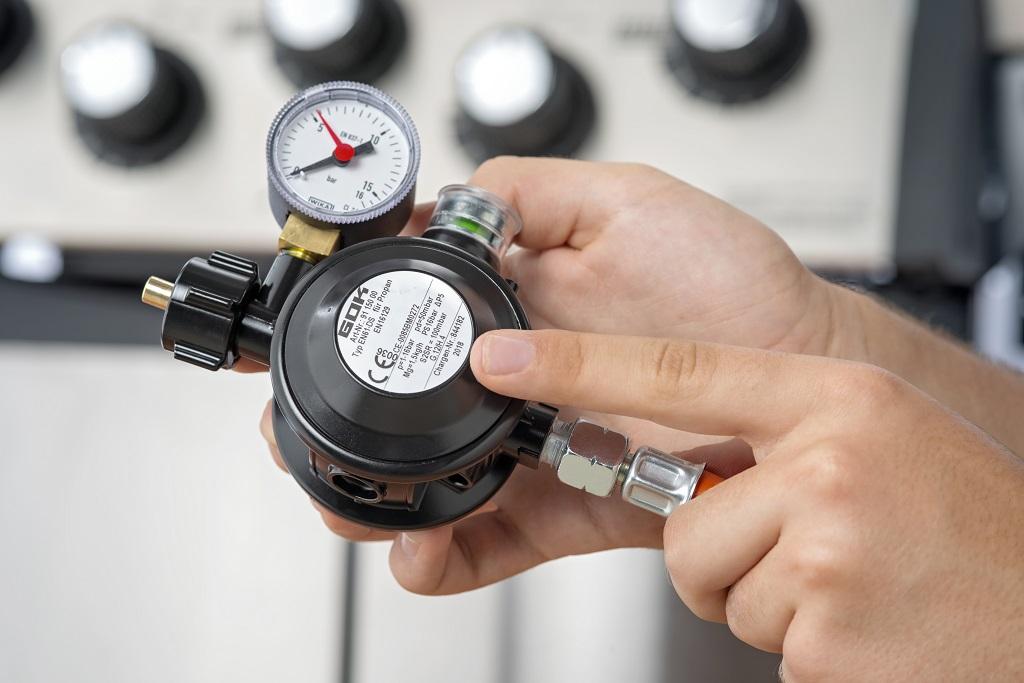 """Die schwarzen Druckregler, """"Grillregler"""" genannt, sind auch speziell für das Grillen mit Flüssiggas ausgelegt. Daher kann der Nutzer den Druckminderer im Freien einsetzen."""